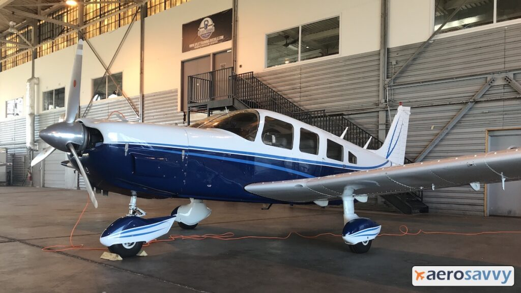 Blue and white single engine, low-wing aircraft parked in a hangar.