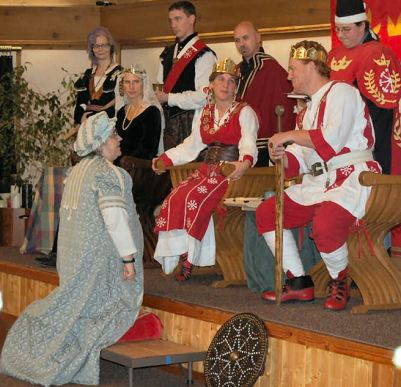 Dame Elsbeth receives an Augmentation of Arms. Photo by Lady Àine ny Allane.