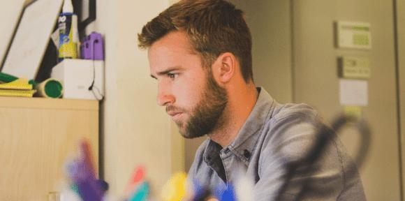 junger Man am Schreibtisch als Symbolbild: Berufliche Handlungsfähigkeit und Gegenstand der Azubi-Abschlussprüfungen