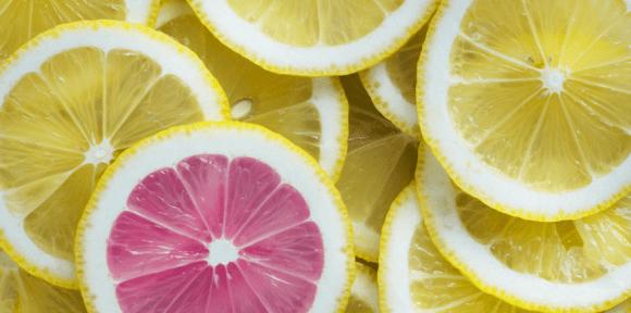 Symbolbild: viele Zitronenscheiben in gelb - eine Pampelmusenscheibe in rot