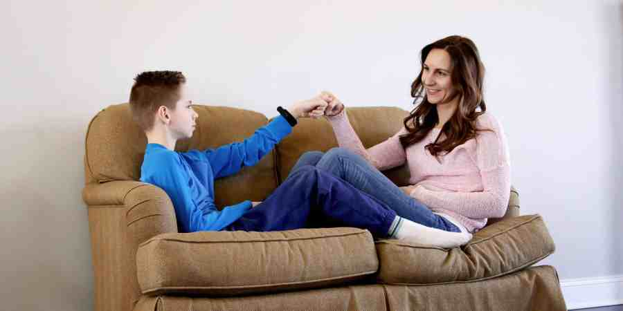 tween boy mom giving fist bump to tween boy while sitting on couch