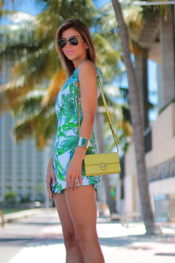 miami fashion lifestyle blogger amanda tur from a fancy affair wearing gucci green wallet on chain bag tropic palm tree romper and henri bendel necklace and dainty bracelet with yorkie toy dog yorkshire and nude sandals perfect for summer
