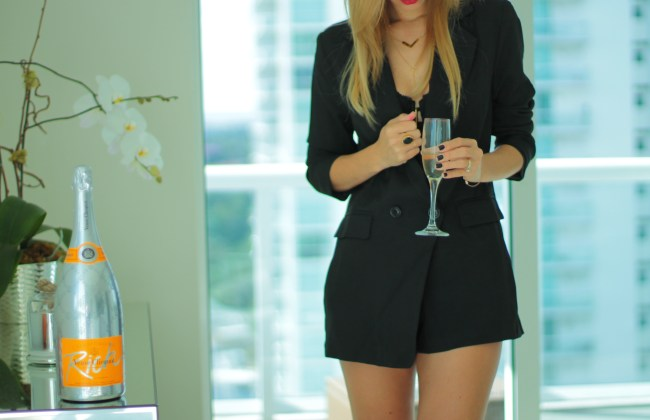 miami blogger lifestyle and fashion blogger amanda tur from a fancy affair wearing the tuxedo blazer romper with schutz cadeey strappy black sandals perfect for fall with a pop of lancome red lipstick labsolu rouge definition 184 le vermillo lipstick and black bralette perfect for fall sashion fall style with margaret elizabeth onyx ring and baublebar olympus layered collar necklace