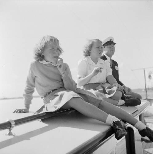 Prinses Beatrix, prinses Irene en prins Bernhard kijken naar voorbij varende sch…