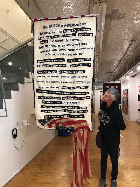 "Maureen takes in the ""James Baldwin Quote #1"" quilt at Gallery Aferro."