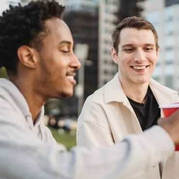 smiling young multiracial students clinking glasses in city street