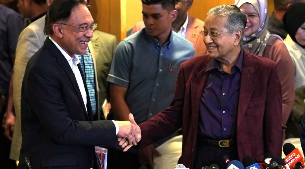 Mahathir and Anwar shake hands.
