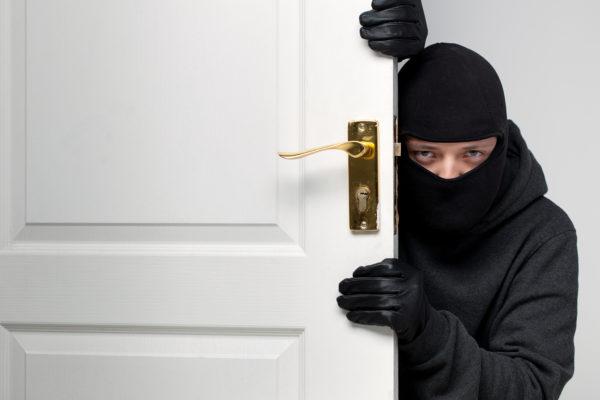 Burglar sneaking in a open house door