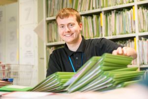 Man in black shirt, with a pile of files in front of him