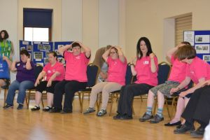 A row of people in pink T-shirts doing exercises