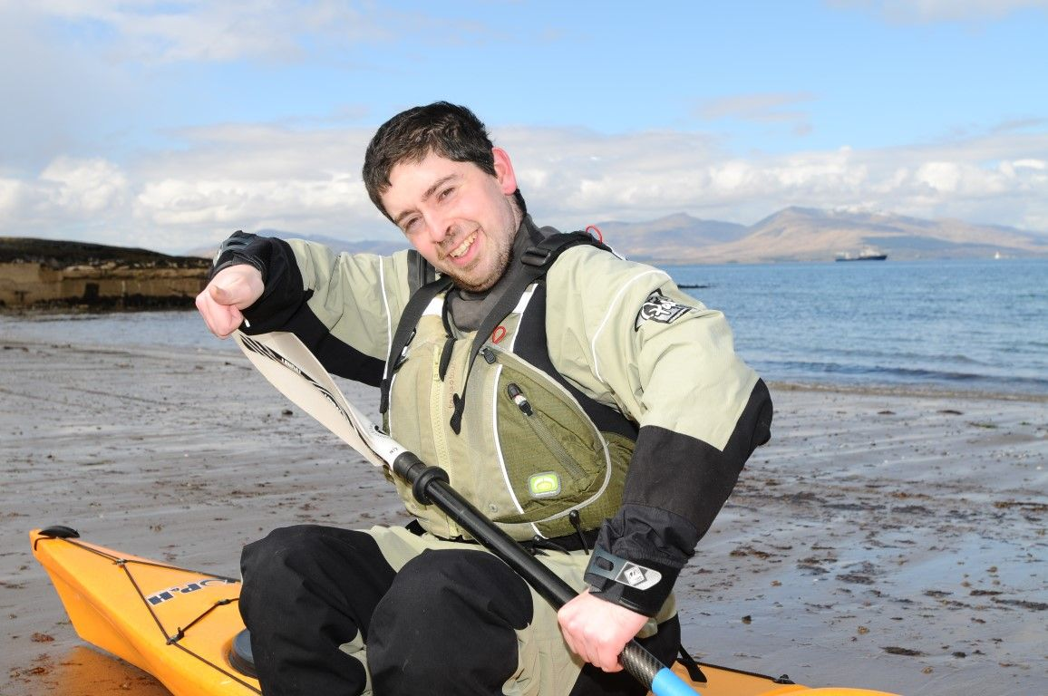 Man sitting on his kayak on a beach in Oban