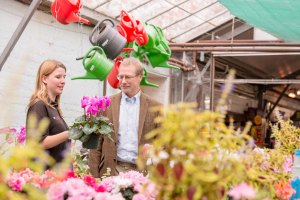 A man and a lady looking at pink flowers in a pot in a garden centre