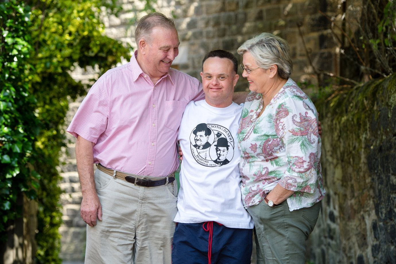 A young man and his parents smiling