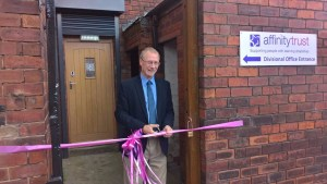 Man cutting a ribbon to open a building