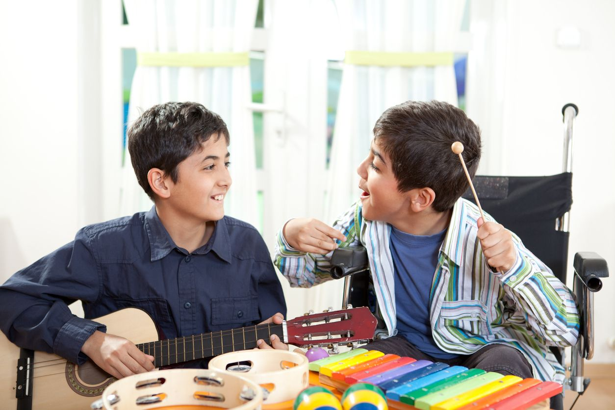 Two children playing musical instruments. One child is in a wheelchair.