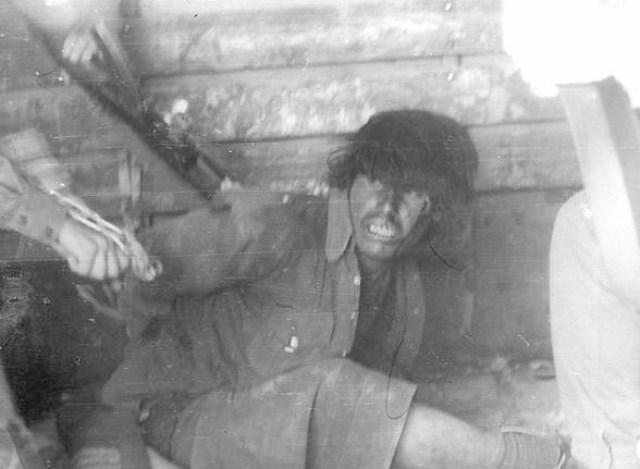 Наши солдаты избивают пленного. Бьют прикладом автомата и железной цепью.