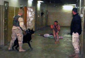 Inside Abu Ghraib prison in Iraq, a US soldier threatens a naked detainee with an attack dog.