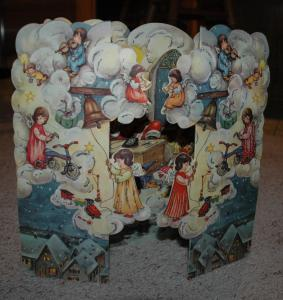 A very old Advent calendar kept by my mom.  Isn't it wonderful?  There are angels...and also Santa inside, sitting at his desk, checking his list.  So fun!