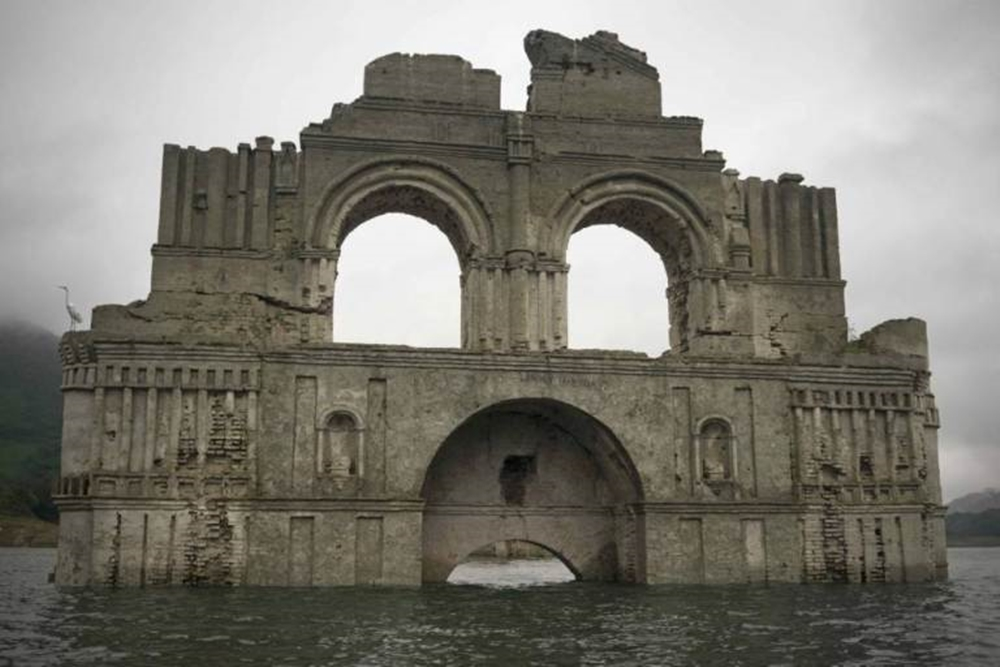 The remains of a mid-16th century church known as the Temple of Santiago, as well as the Temple of Quechula, is visible from the surface of the Grijalva River, which feeds the Nezahualcoyotl reservoir, due to the lack of rain near the town of Nueva Quechula, in Chiapas state, Mexico, Friday, Oct. 16, 2015. It's the second time this has happened. In 2002, the water was so low visitors could walk inside the church. (AP Photo/David von Blohn)