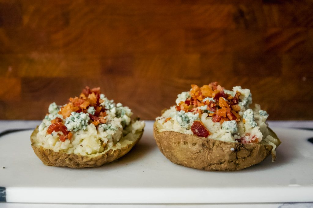 rich blue cheese + butter, smoky bacon, and cream are combined and stuffed into these twice baked potatoes for a gourmet touch at your next family meal! blue cheese, butter + bacon stuffed twice baked potatoes | a flavor journal food blog