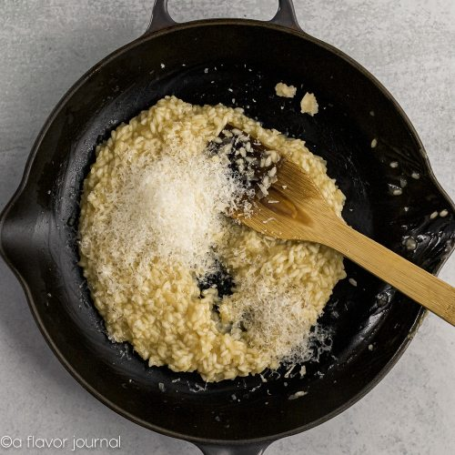 A cast iron skillet with olive oil, onions, garlic, arborio rice, and chicken stock cooking in it and topped with grated parmesan cheese to make parmesan risotto.