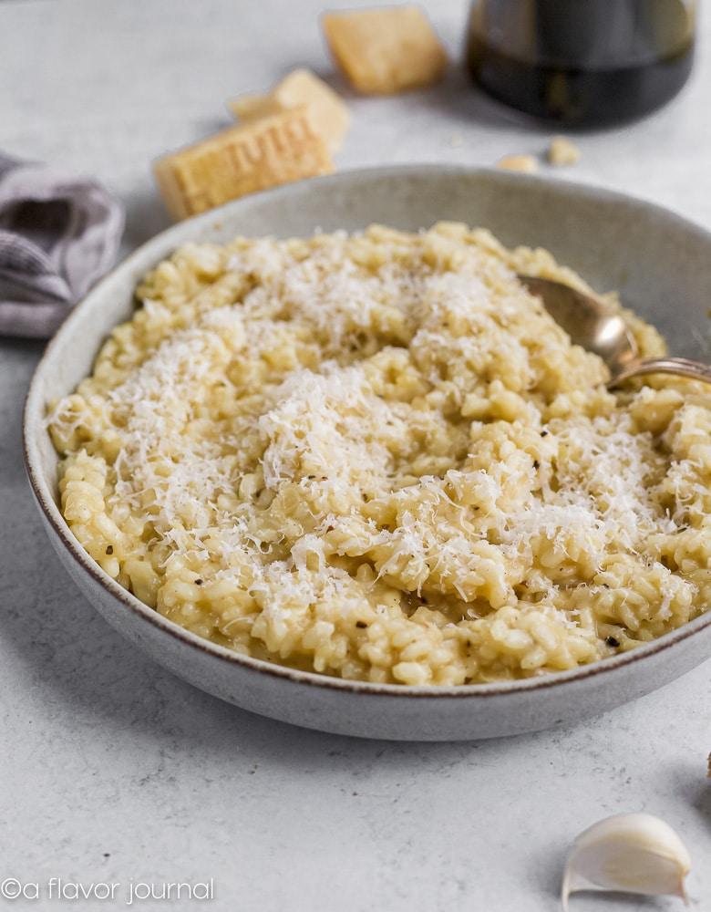 A light gray bowl full of creamy parmesan risotto with finely grated parmesan on top.