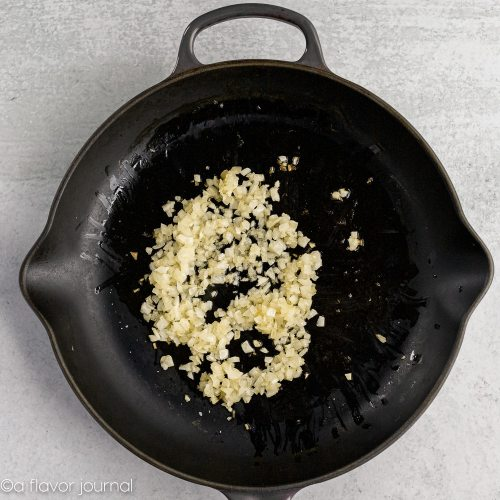 A cast iron skillet with olive oil and onions cooking in it.