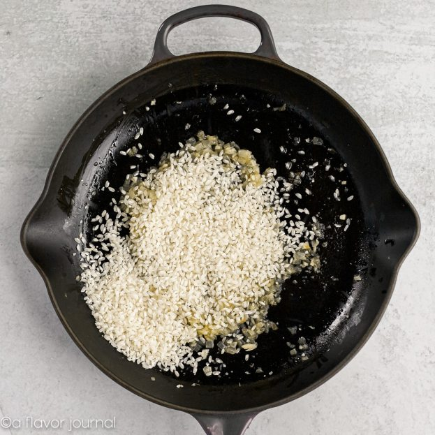 A cast iron skillet with olive oil, onions, garlic and dried arborio rice cooking in it.