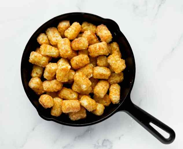 Crispy tater tots in a cast iron pan