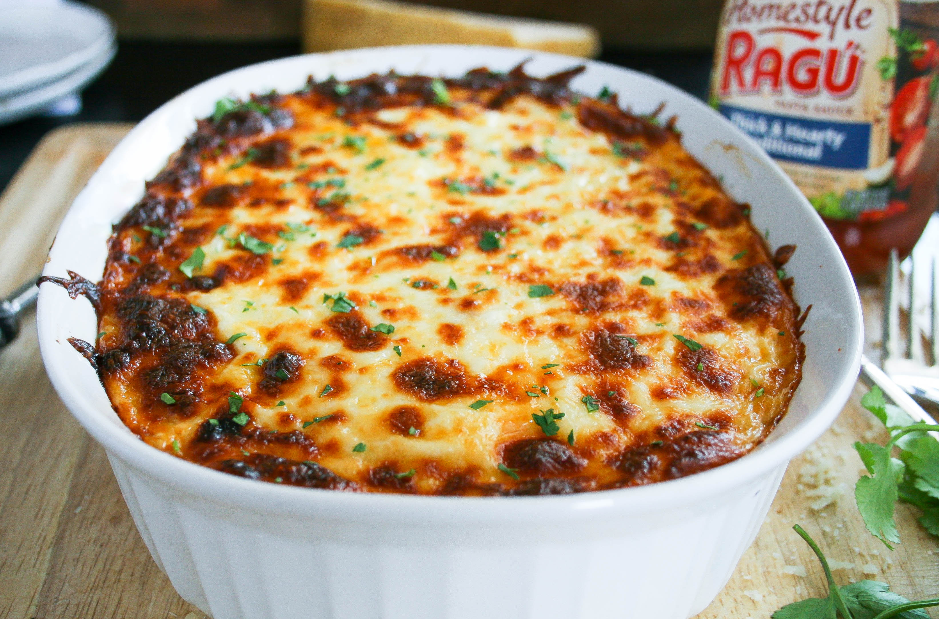 favorite pasta bake combines hearty tomato sauce, hot italian sausage, and ground beef with layers of creamy, cheesy sauce! this pasta bake is topped with mozzarella cheese and baked to perfection. and instant family favorite! | a flavor journal