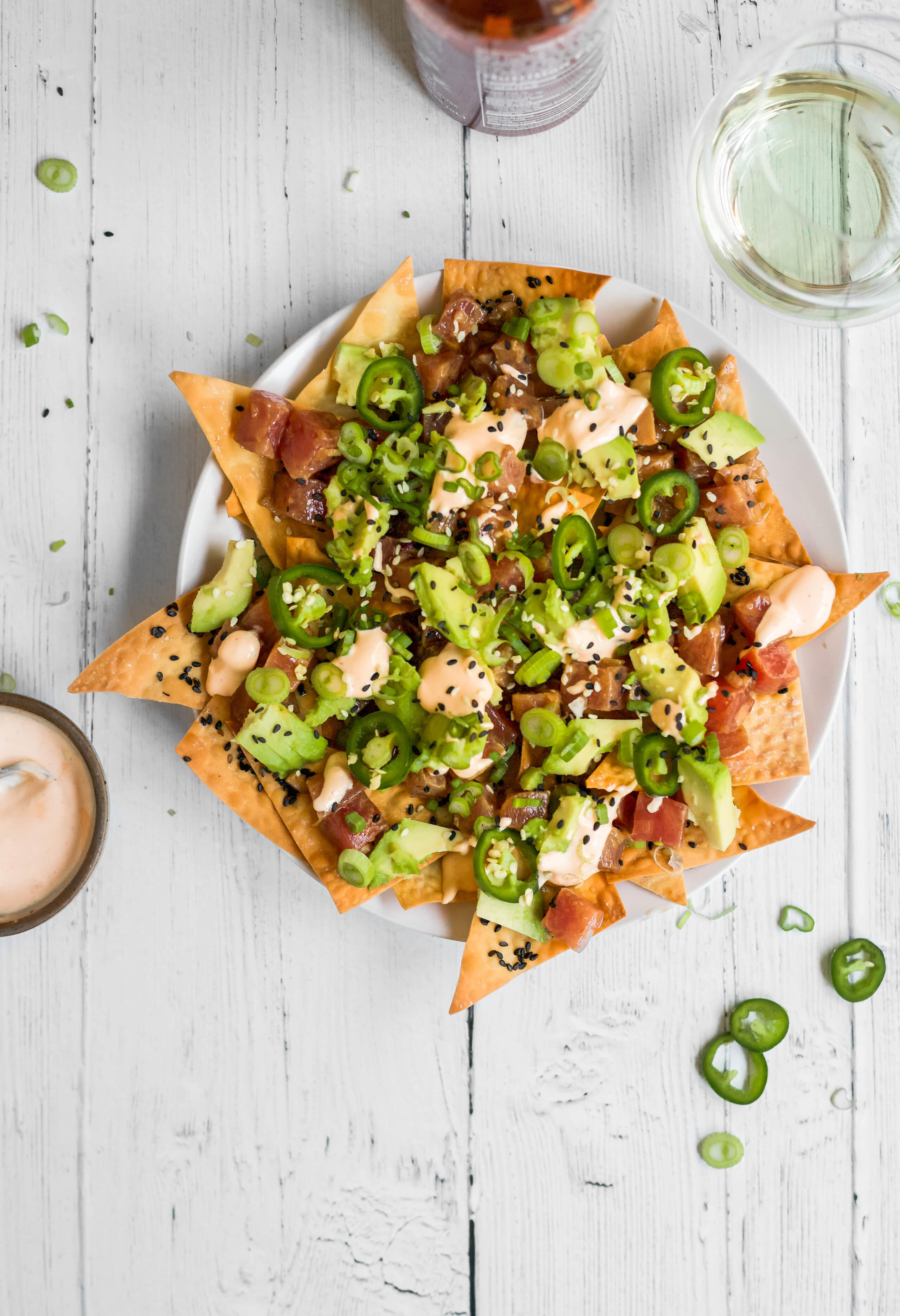 spicy tuna tartare nachos recipe :: baked, crispy wonton chips, spicy ahi tuna, creamy avocado, and spicy sriracha sauce. DELICIOUS and perfect for happy hour at home or date night in! spicy tuna tartare nachos | a flavor journal food blog