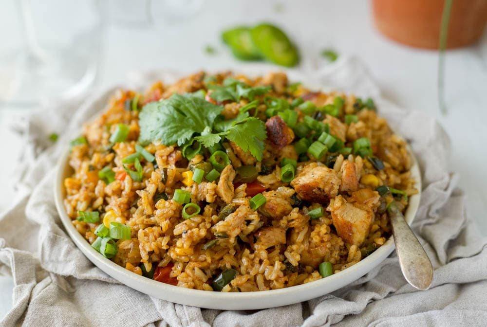 an easy tex-mex chicken dish with fajita veggies, spices, shredded chicken, and leftover rice!