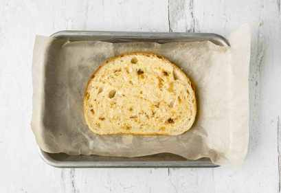 A slice of sourdough bread smothered in roasted garlic butter, set on top of a small baking sheet lined with parchment paper.