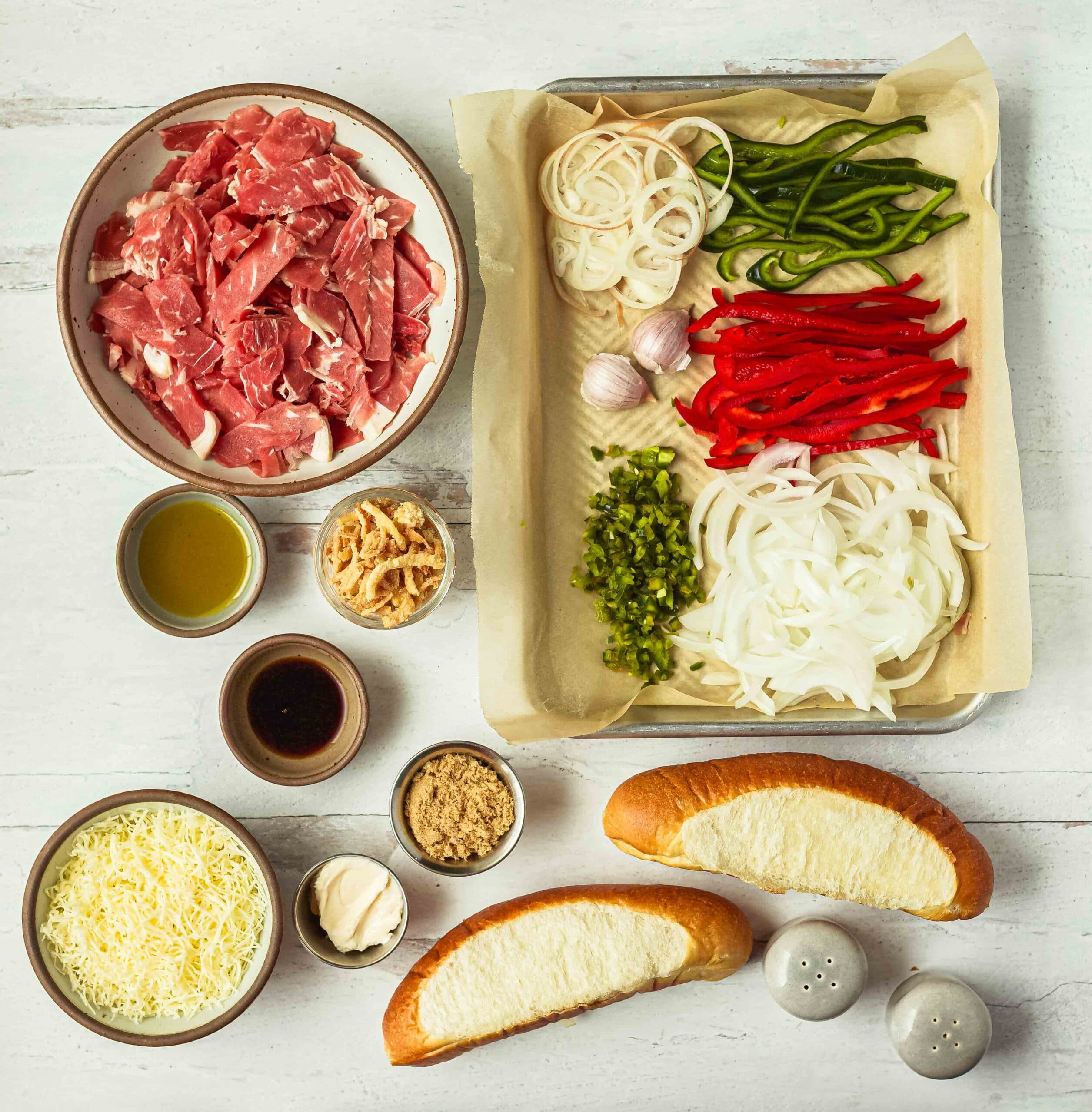 Ingredients laid out for a philly cheesesteak sandwich: sliced ribyee, onions, poblano peppers, red peppers, jalapenos, garlic, shallots, brown sugar, soy sauce, french fried onions, shredded cheese, mayonnaise, olive oil, hoagie buns, and salt and pepper shakers.