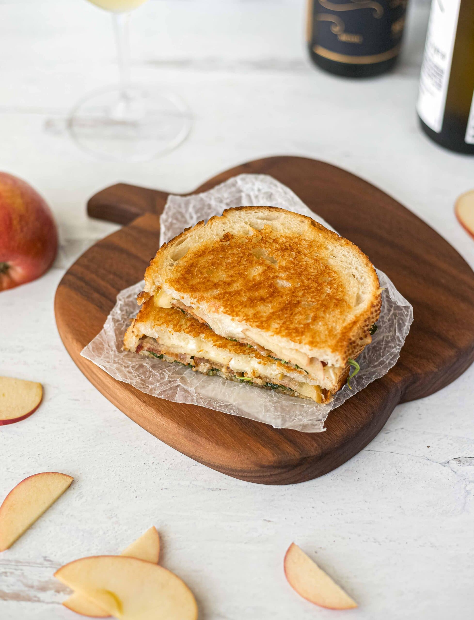 A grilled cheese sandwich on an apple shaped cutting board with a bottle of wine in the background