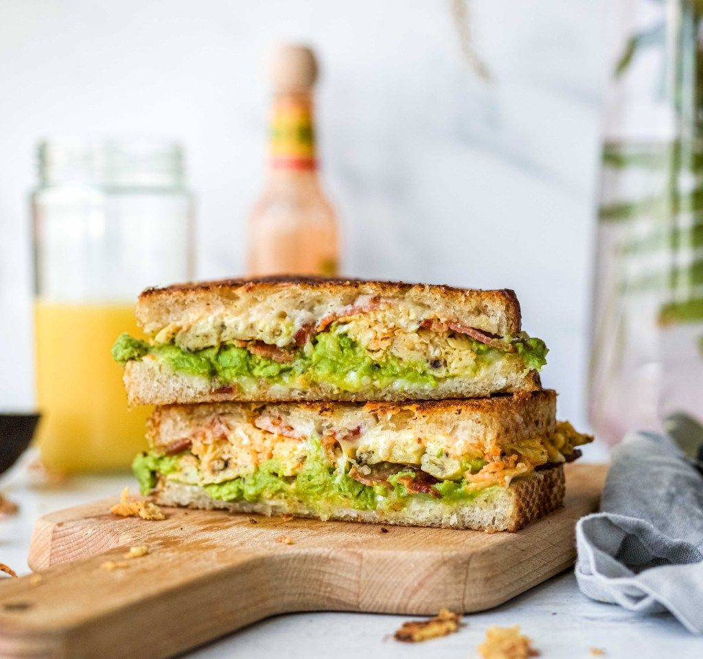 A grilled cheese sandwich with scrambled eggs, bacon, cheese, and avocado resting on a cutting board with hot sauce and orange juice in the background.