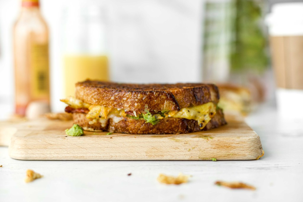 A grilled cheese sandwich with scrambled eggs, bacon, cheese, and avocado resting on a cutting board with hot sauce, orange juice and a coffee cup in the background.