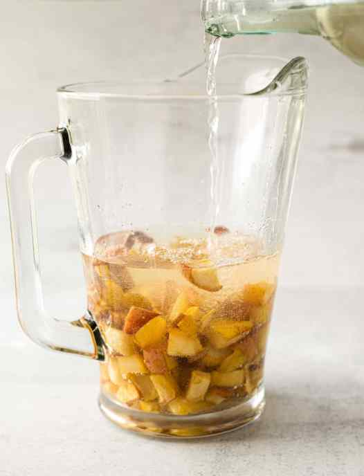 A large glass pitcher of baked pear and apple fall sangria with white wine being poured into it.
