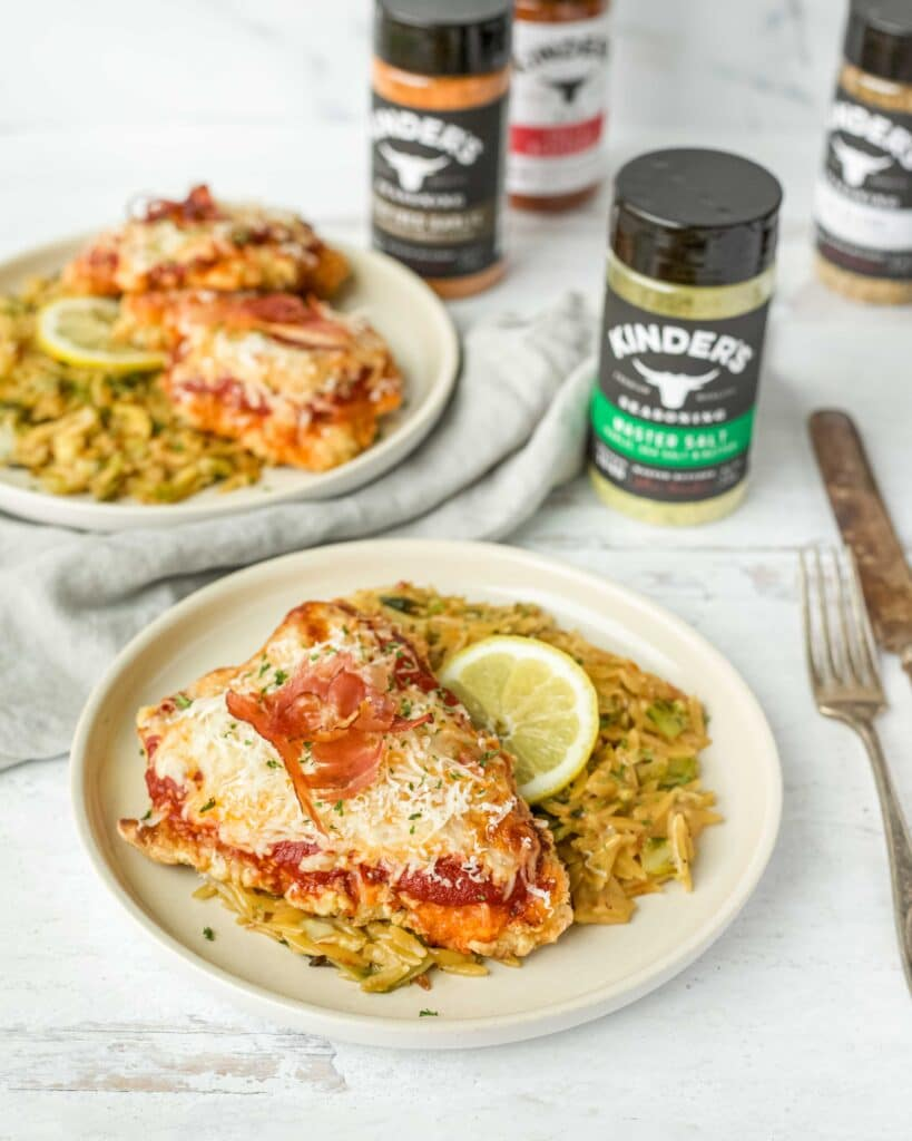 Crispy chicken parmesan on top of creamy brussels sprouts orzo plated on a small cereamic plate with a gray linen and Kinder's® Master Salt Seasoning blend in the background