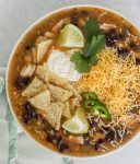 A big bowl of chicken tortilla soup with black beans, shredded cheese, jalapenos, limes, tortilla chips, sour cream, and cilantros.