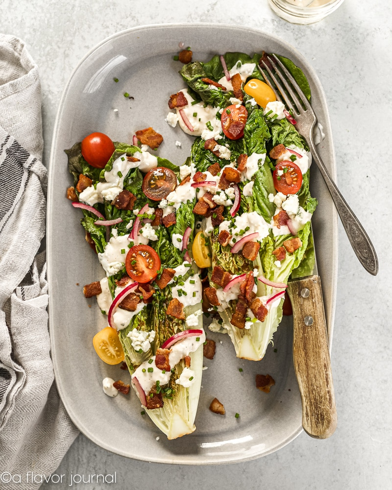 A head of romaine cut in half a grilled, placed on a gray platter, then topped with tons of wedge salad toppings.