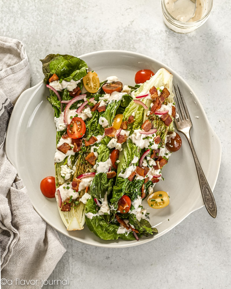 A circular gray platter topped with a grilled romaine wedge salad.