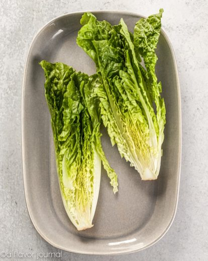 A gray platter with two halves of romaine placed on it.