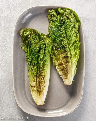 A gray platter with two halves of grilled romaine placed on it.