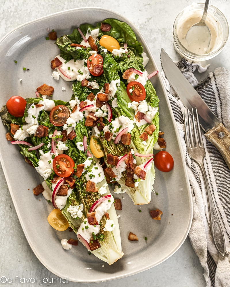 The perfect grilled romaine salad is a twist on the classic wedge salad. This grilled romaine wedge is piled with homemade blue cheese dressing, fresh cherry tomatoes, crunchy bacon, green onion, french fried onions, pickled red onions, and freshly cracked black pepper.