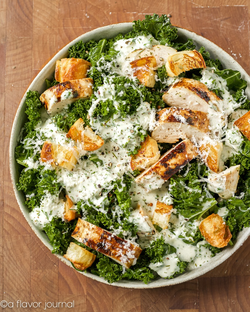 A large bowl of massaged kale, toasted croutons, and grilled chicken topped with a creamy buttermilk dressing.