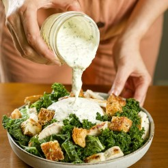 Creamy asiago buttermilk dressing being poured on top of a chicken kale salad.