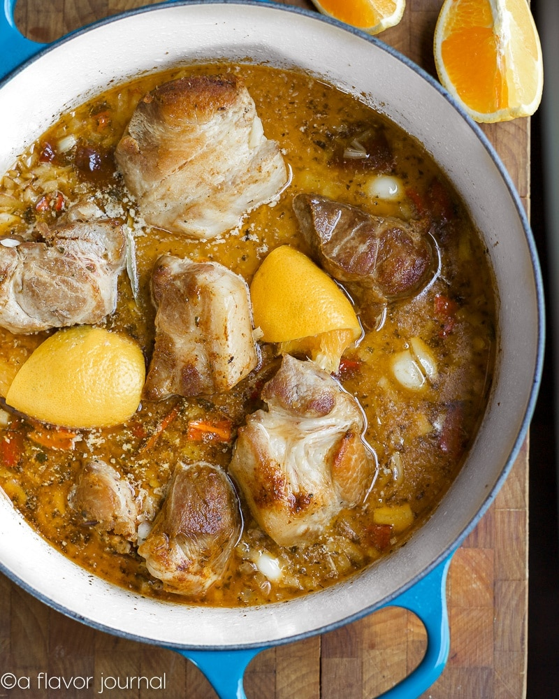 A dutch oven full of pork, spices, vegetables, and broth for pork carnitas.