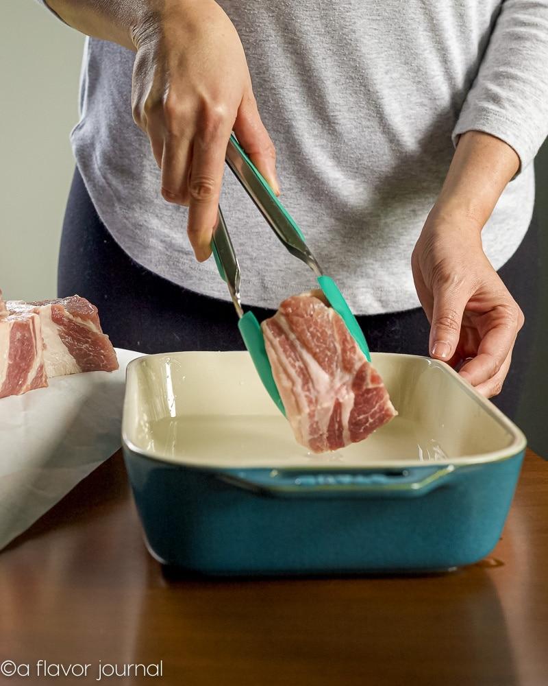 Placing pork pieces into a salt bine for pork carnitas.