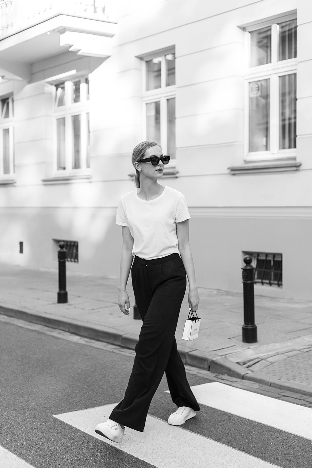 Girl in white t-shirt and black palazzo pants with Chanel makeup bag
